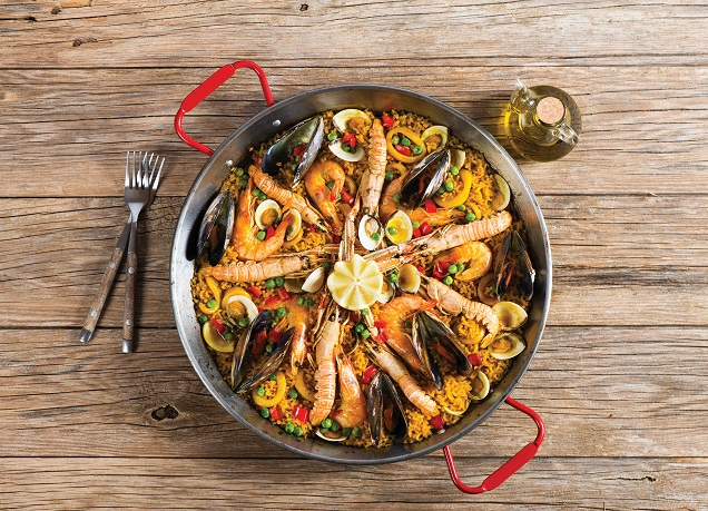 View from above of paella with seafood in a paellera on a wooden background with copy space